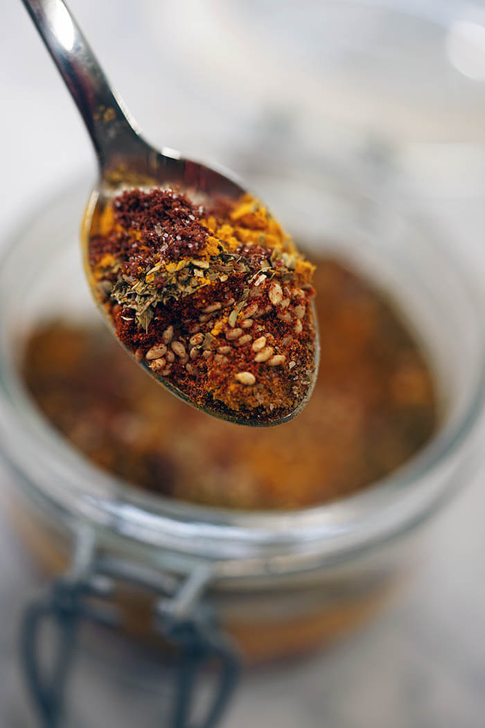 A clear jar filled with a homemade spice rub recipe. There's a close up picture of a scoopful of the rub.