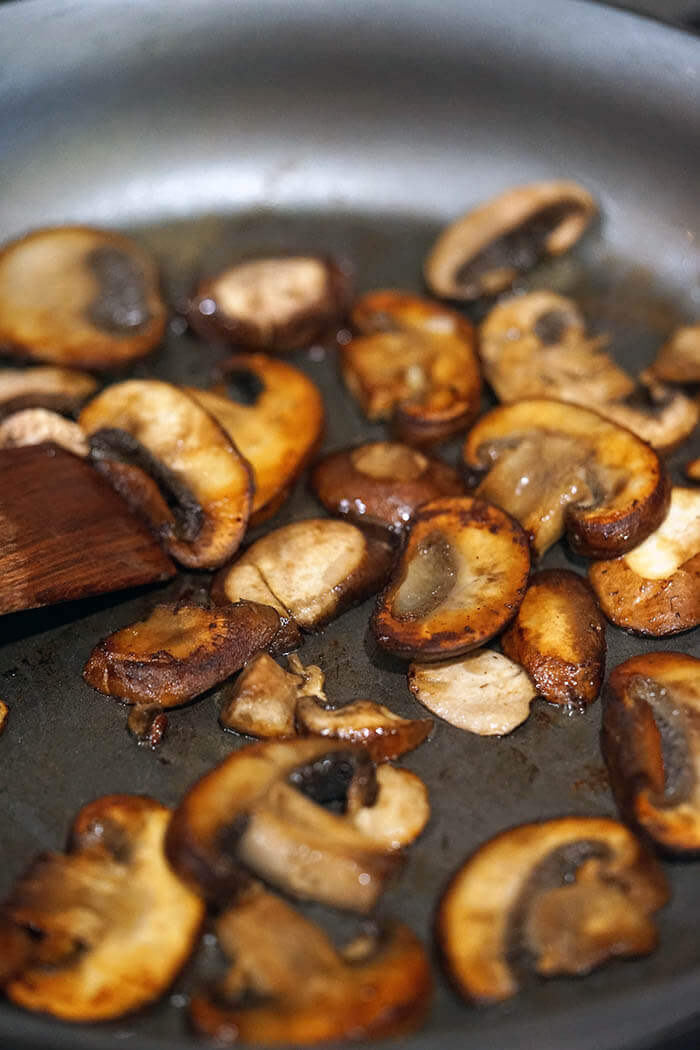 A skillet with sautéed mushrooms.