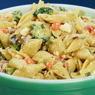A green bowl filled with Pasta Salad with Cheese, Ham and vegetables.