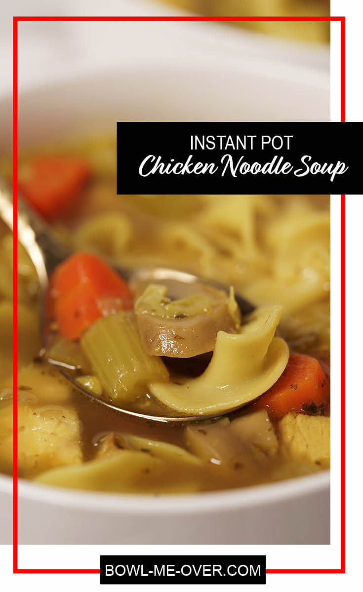 A big bowlful of hearty chicken noodle soup. A spoon is filled with a big bite containing noodles, celery, chicken, carrots and mushrooms - enjoy!