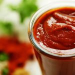 Best enchilada sauce in a glass jar surrounded by herbs and spices.