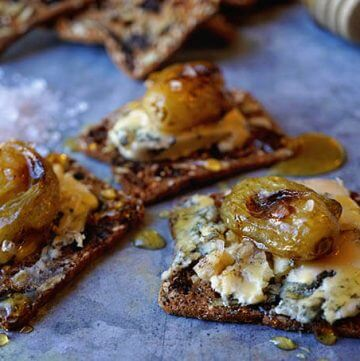 A silver platter filled with appetizers. This is a roasted grape crostini recipe