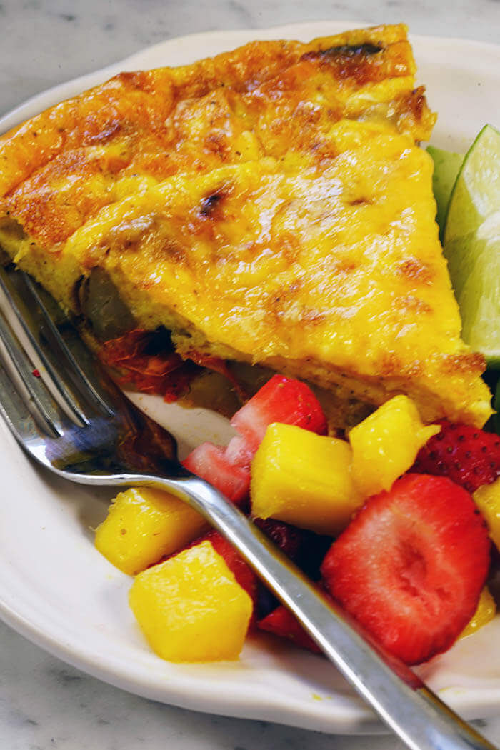 An easy frittata recipe pictured here. A white plate with a wedge of frittata served with avocado slices and fruit salad.