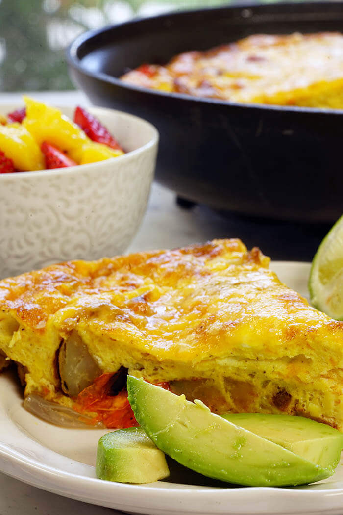 A white plate with a wedge of frittata served with a side of avocado and fresh fruit. This is a recipe for an easy frittata