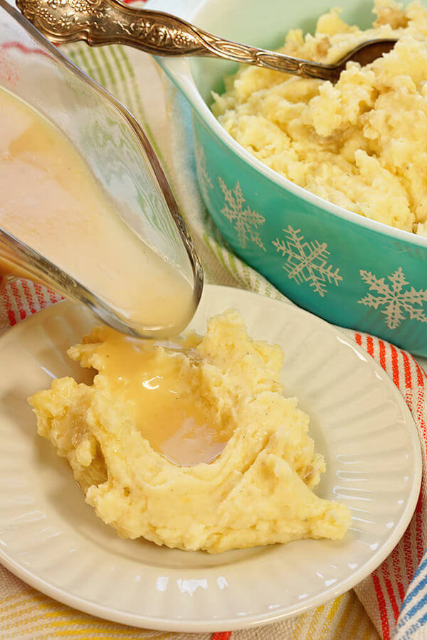 A white place with mashed with gravy being poured overtop. Instant pot mashed potatoes with homemade made gravy.