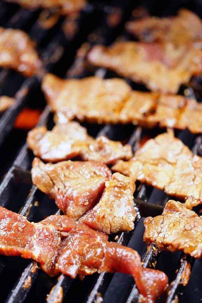 Slices of beef on a hot grill being cooked.