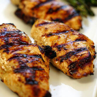 A white platter with chicken that's been grilled with lemon pepper marinade.