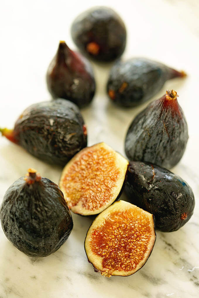 Ripe figs scattered on a white marble counter. Ripe and delicious black mission figs are succulent and amazing.