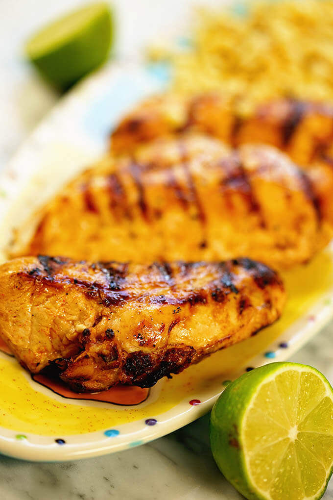 A platter of grilled chili lime chicken breast with a wedge of lime to squeeze over top.