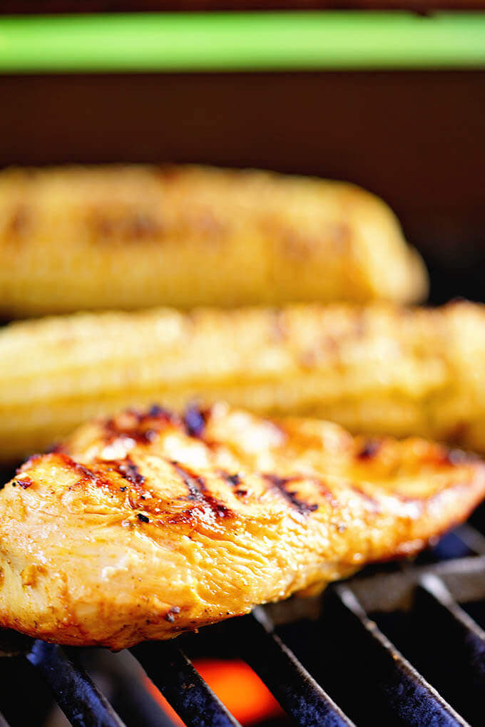 A hot grill with chili lime chicken and sweet corn sizzling on the grill.