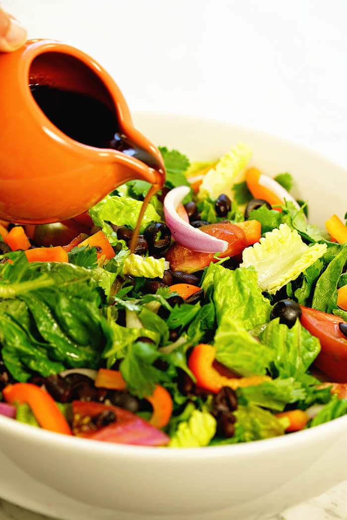 Easy southwest salad recipe being topped with a homemade vinaigrette pour from an orange container.