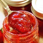 A jar of strawberry jam with a spoon dishing out the bottom of the jar!