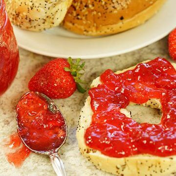 Homemade strawberry jam spread on a bagel.
