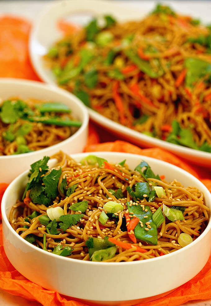 A white bowl filled with teriyaki noodles. The noodle bowl is mixed with green onions, shredded carrots and snow peas. Topped with sesame seeds and cilantro.