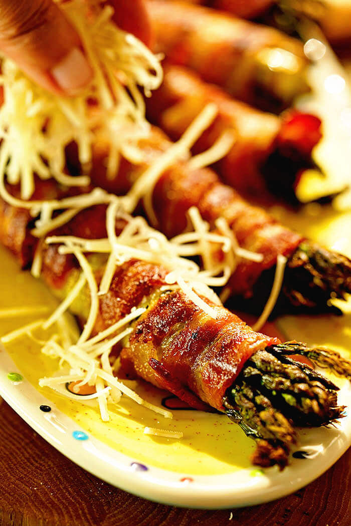 A platter of asparagus wrapped in bacon being sprinkled with parmesan cheese.