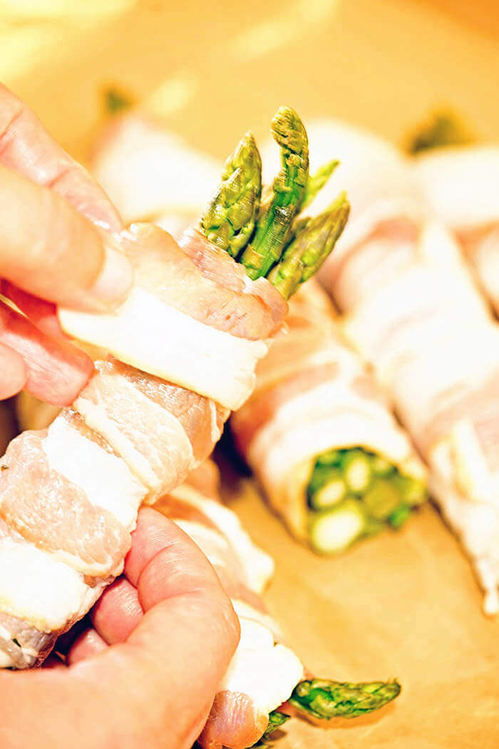 Bundles of fresh asparagus being wrapped by thin sliced bacon.
