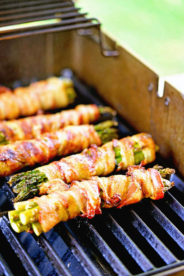 Asparagus wrapped in bacon being cooked on the grill.