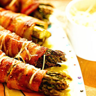 A platter of grilled asparagus wrapped in bacon sprinkled with shredded parmesan cheese on a platter.