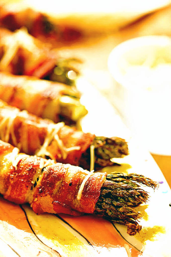 A platter of asparagus wrapped in bacon cooked on the grill.