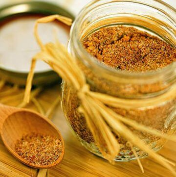 A small jar filled with sweet rib rub. There's a spoonful off to the side.