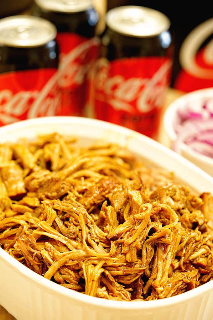 Instant Pot Pulled Pork in a white dish surrounded by soda pop.