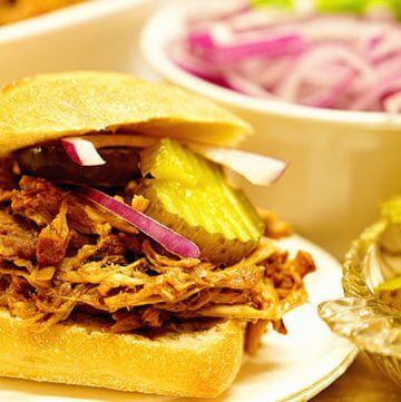 BBQ Pulled Pork Sandwich Recipe with red onions and pickles.