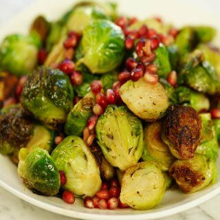 Brussels Sprouts in white bowl topped with pomegranate seeds.