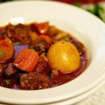 Lamb stew recipe served in a white bowl. The stew is full of tender lamb morsels and big chunky vegetables.