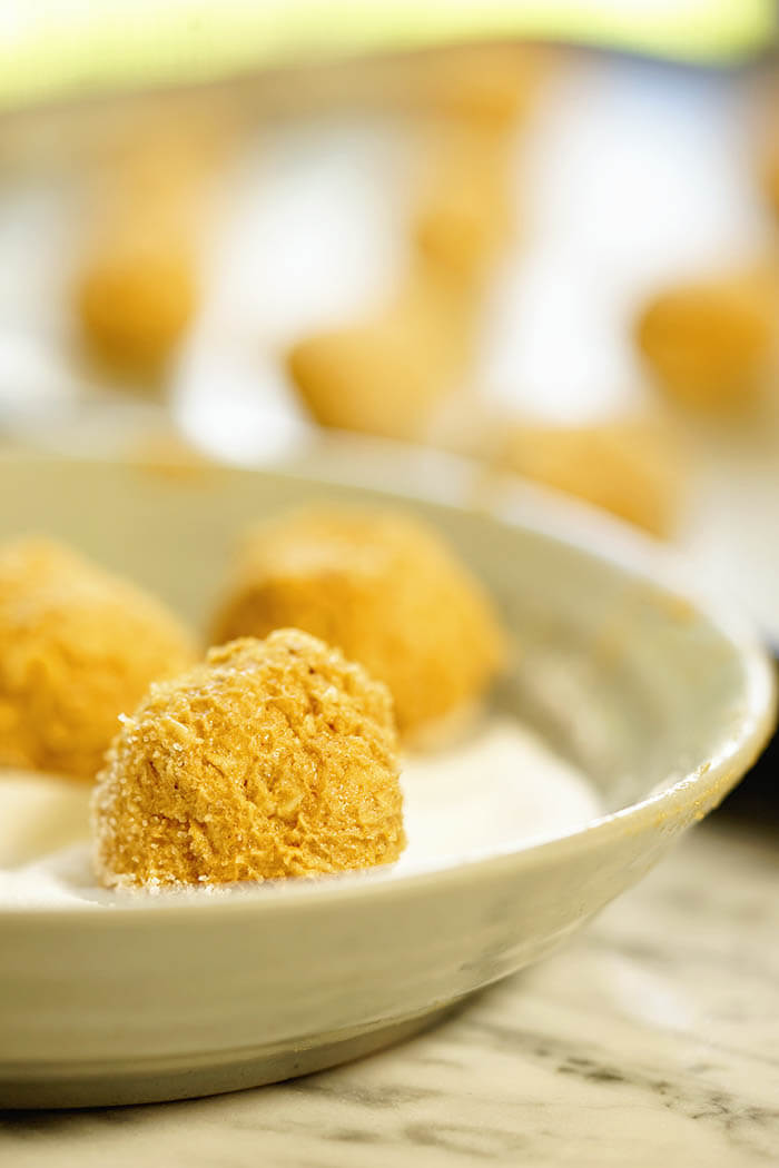 Raw cookie dough balls being rolled in sugar.