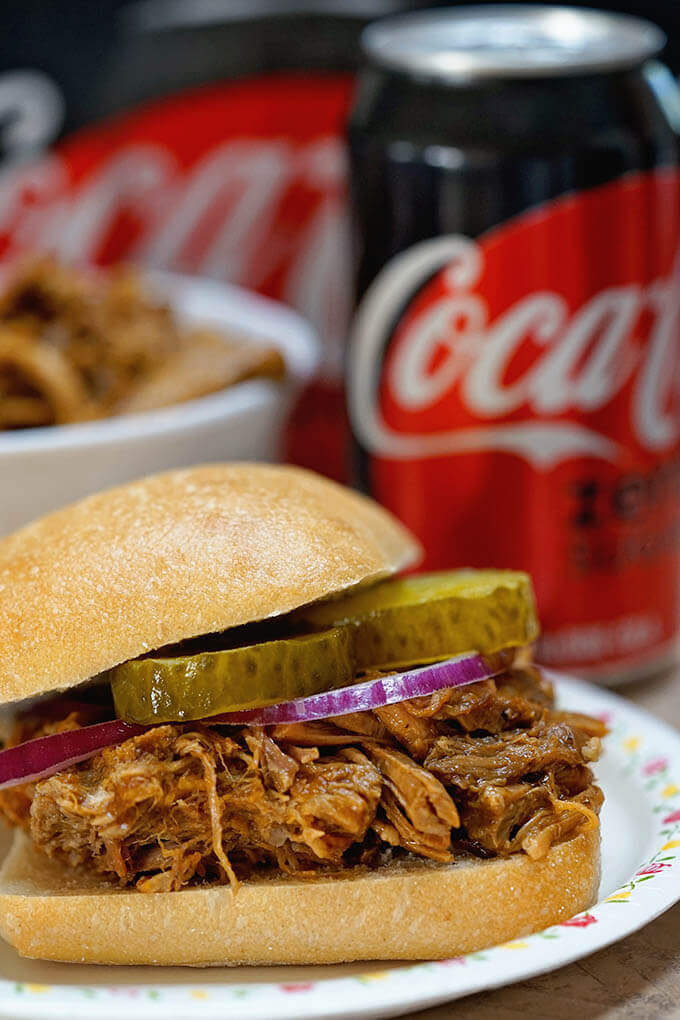 BBQ Pulled Pork Recipe piled on a bun with pickles and red onion surrounded by soda.