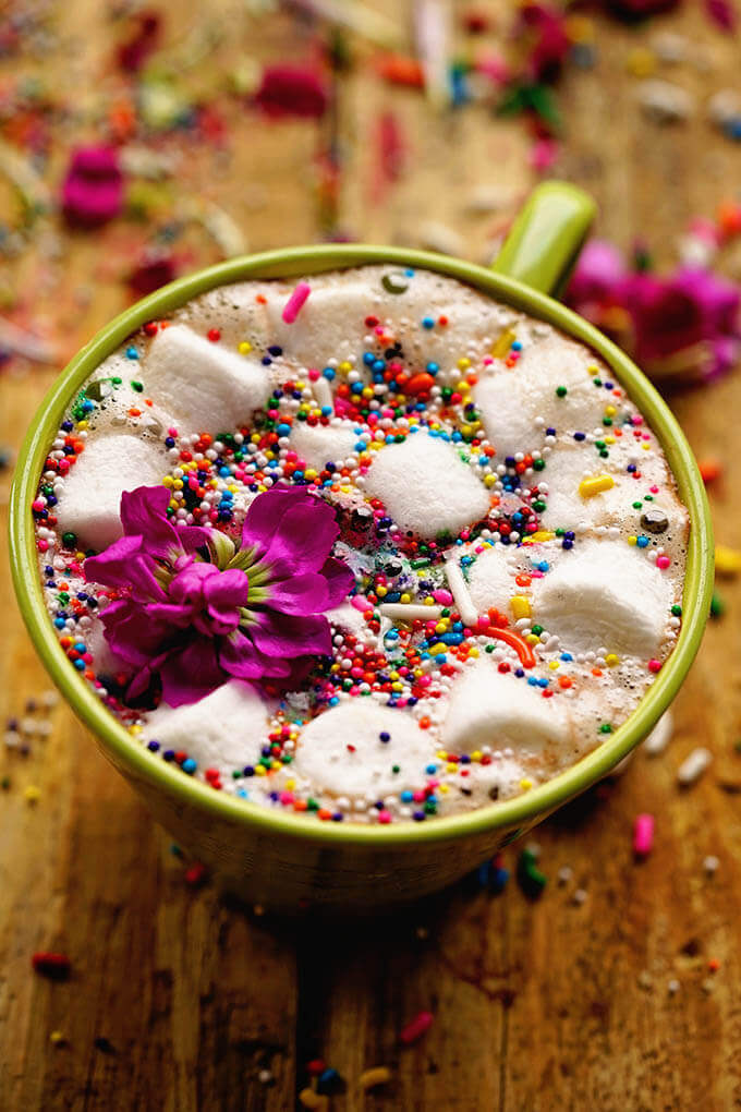 An overheat view of a mug of crock pot hot chocolate on a wood board topped with marshmallows and surround by chocolates.