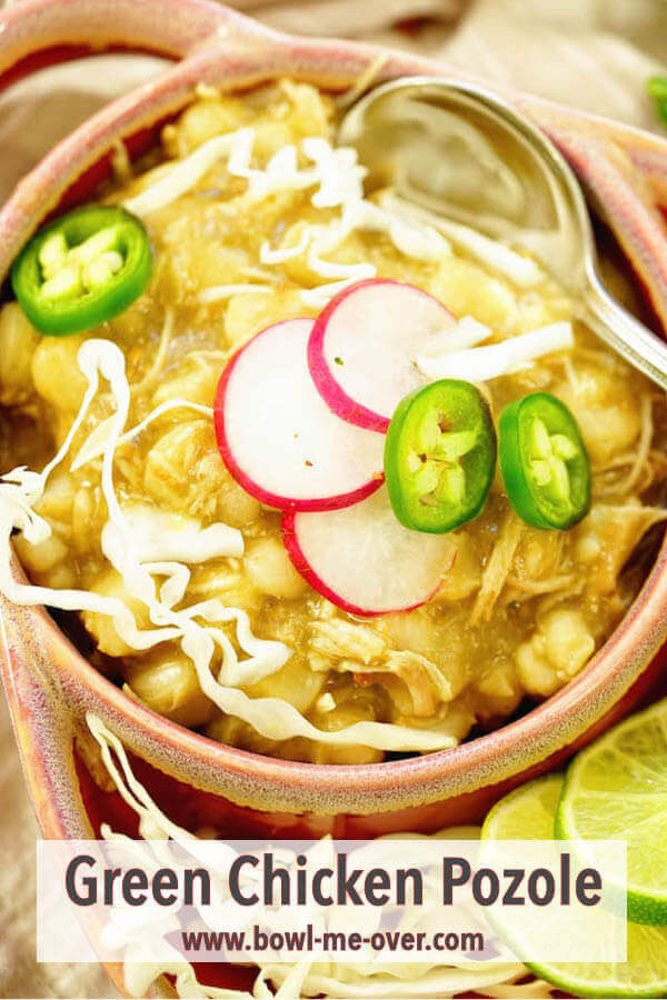 A bowl of green chili pozole topped with radishes, jalapeños and cabbage.