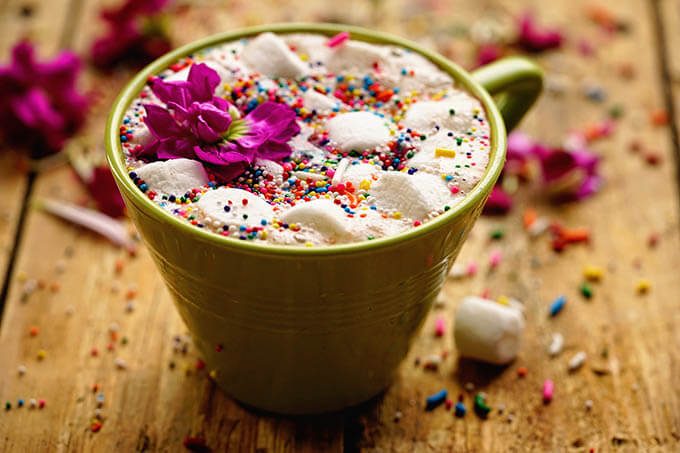 A green cup on a wooden board filled with crock pot hot chocolate, topped with sprinkles!