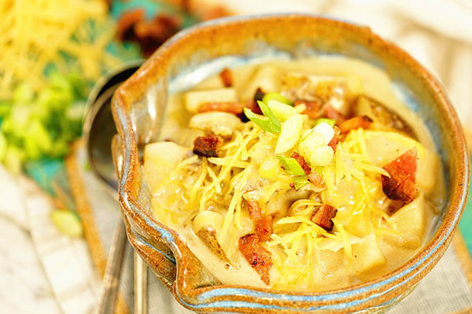 Loaded Potato Soup Recipe topped with cheese, onions and bacon in a blue bowl on a white counter.