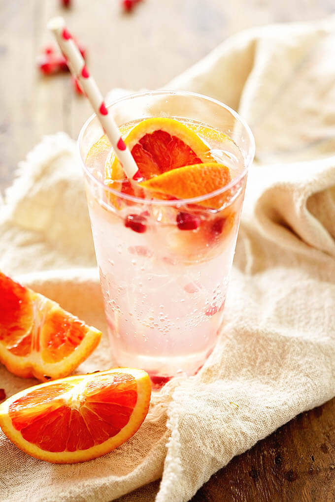 Paloma Cocktail in a clear glass garnished with blood oranges and pomegranate arils.