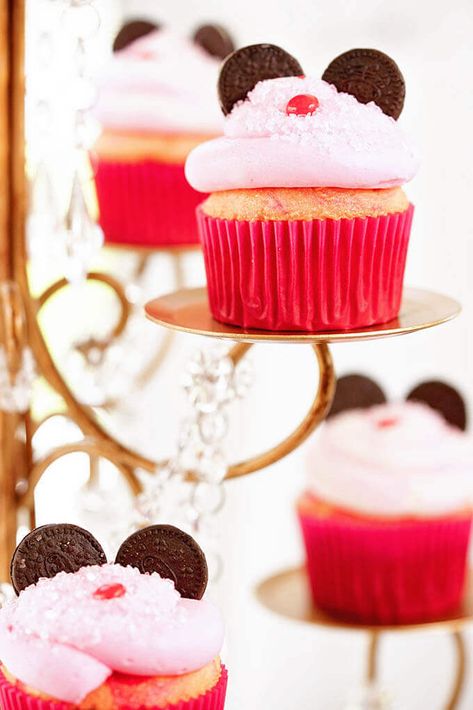 Minnie Mouse Cupcakes with pink frosting and cookie ears on a gold stand