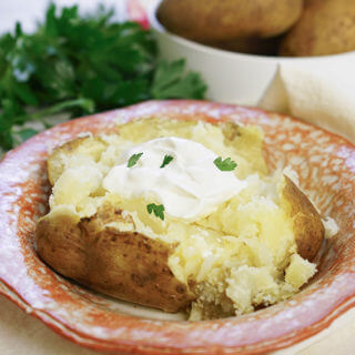 Instant Pot baked potatoes in a bowl topped with butter, sour cream and chives.