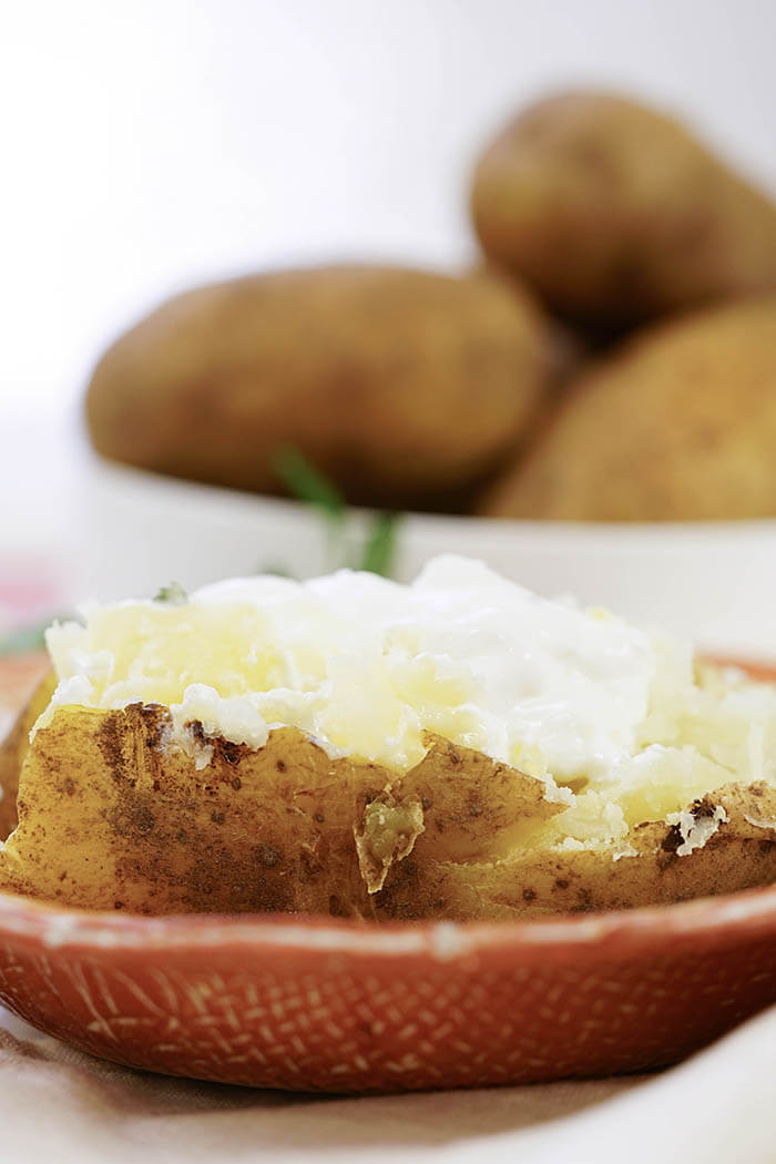 Baked potatoes in the pressure cooker topped with butter and sour cream.
