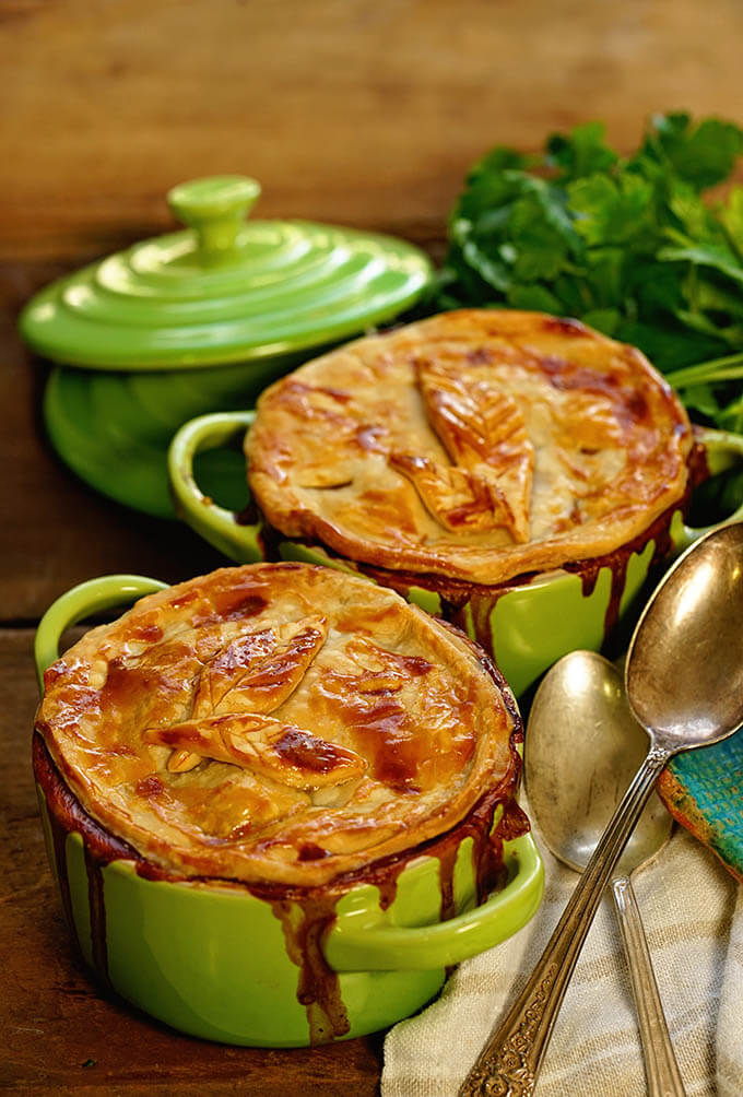 Two green ramekins filled with homemade turkey pot pie baked with a golden crust.