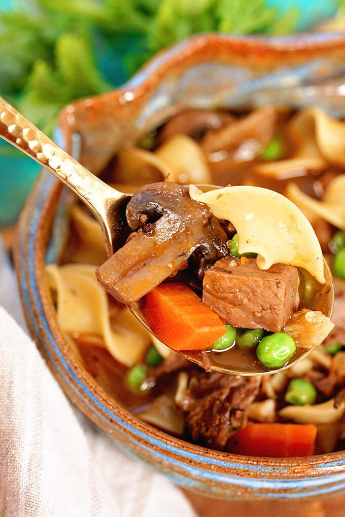 A spoonful of beef noodle soup with mushrooms, carrots, beef, green peas and noodles.