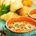 Two bowls of Chicken and Wild Rice Soup Recipe with croissants.