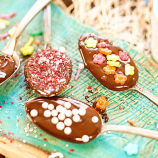 A blue platter with four chocolate covered spoons. Each spoon is topped with sprinkles.
