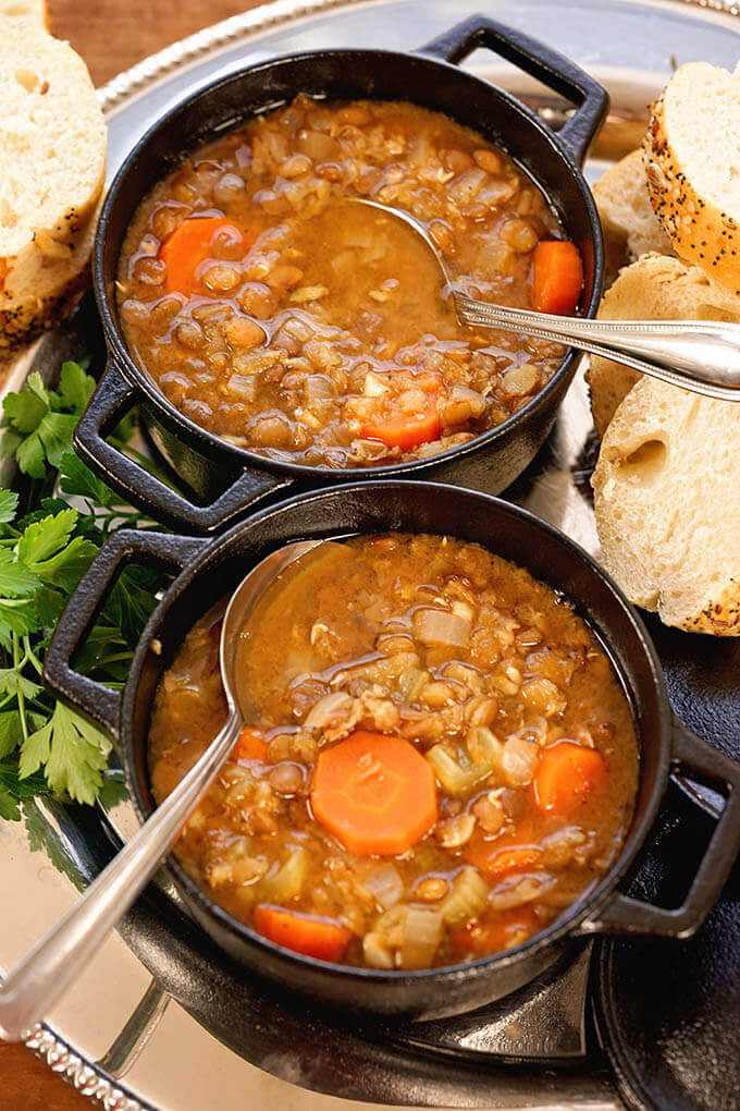 Greek Lentil Soup in two bowls served with a slice of bread.
