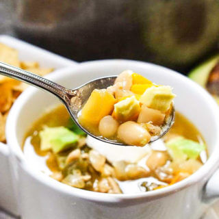 A white mug filled with white bean turkey chili with spoon.
