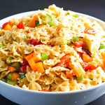 White bowl filled with Italian bow tie pasta salad.