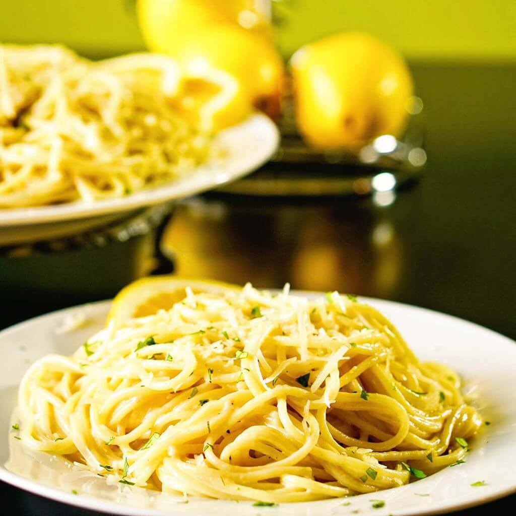 A platter of pasta with lemon cream sauce on white plate.