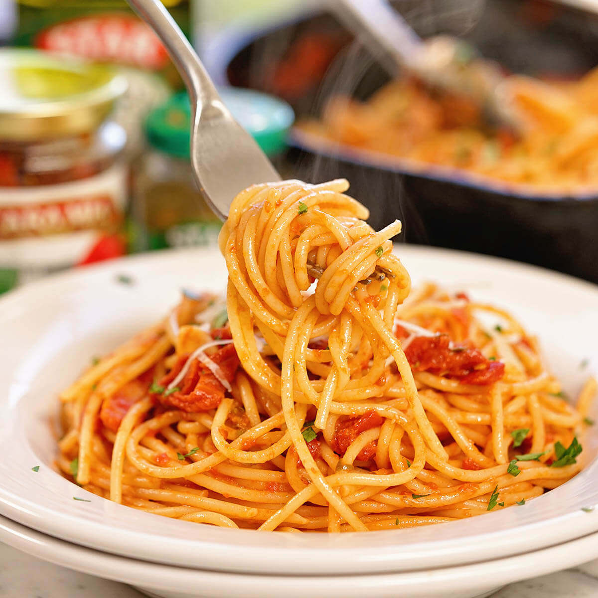 Pasta in white bowl, twirled with a fork