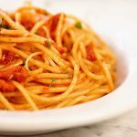 Spaghetti Puttanesca in a white bowl