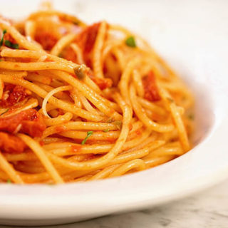 Spaghetti Puttanesca in a white bowl