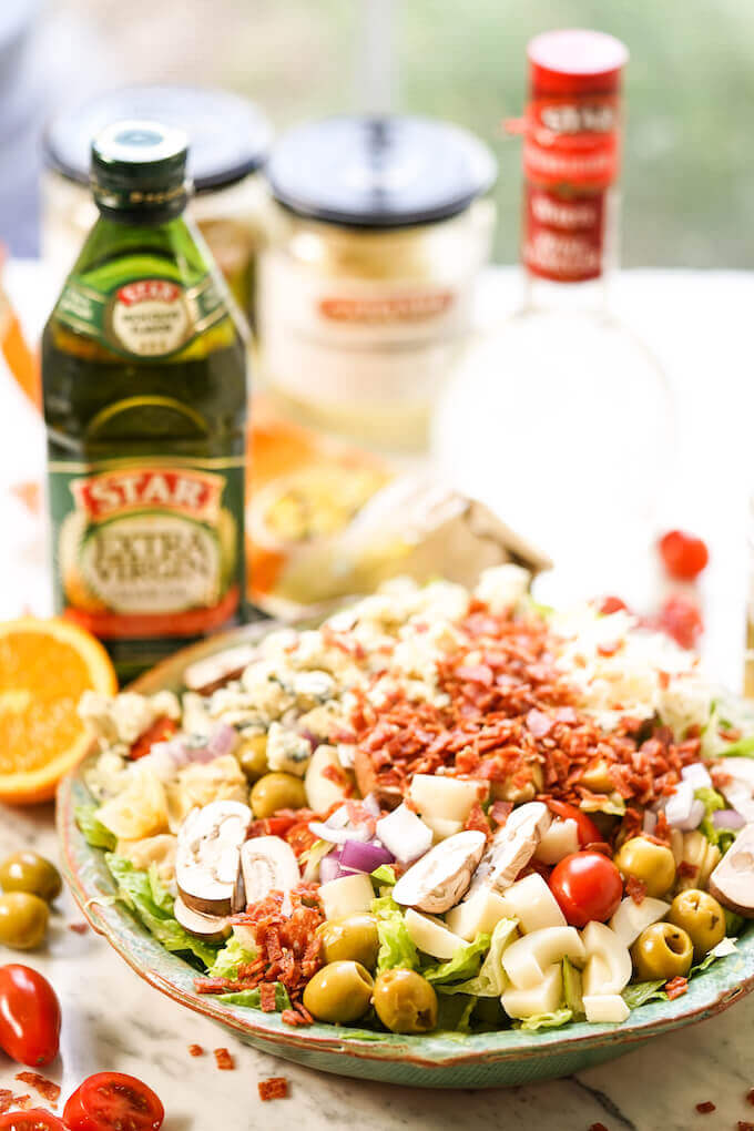 Steakhouse salad topped with fried salami, olives, tomatoes, mushrooms and artichokes with olive oil.